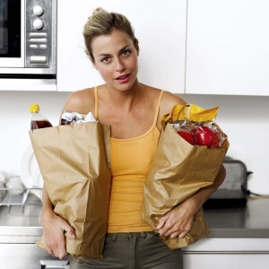 Young Woman Holding Two Brown Paper Grocery Bags