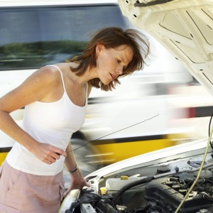 Young Woman Standing Over a Car Engine Bay Checking An Oil Dipstick