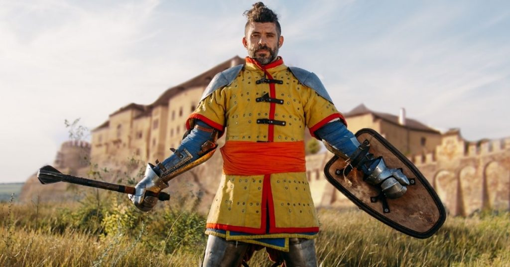 knight in armor in front of castle