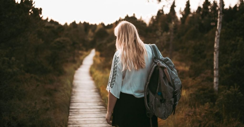 young woman carrying heavy bag and walking on path
