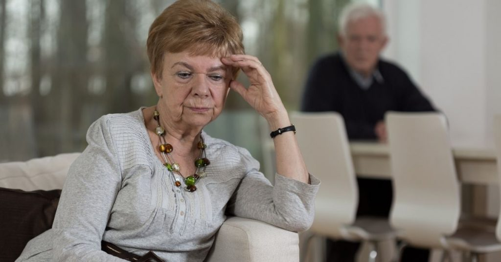 woman looking resentful with man in background